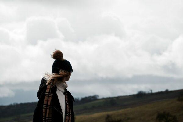 Une personne emmitouflée qui regarde au loin dans la campagne