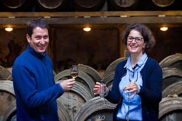 Line Sauvant et son mari devant leur tonneaux, chacun avec un verre à la main.